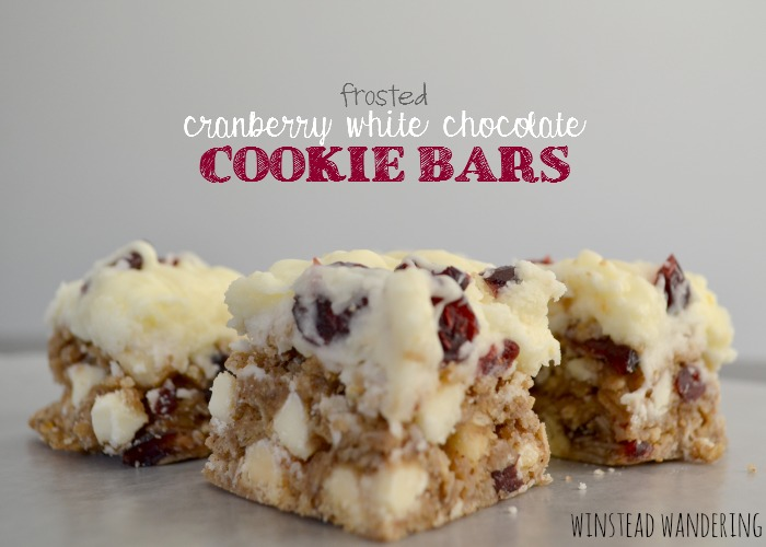 A hearty oat cookie bar base, packed with cranberries and white chocolate chips, spread with a thick layer of white chocolate cream cheese frosting, and topped off with more cranberries and a white chocolate drizzle.