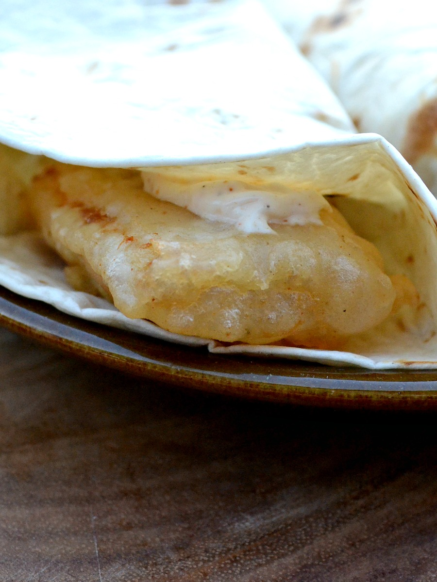 White fish is lightly battered, fried until crispy, and served with a slightly-spicy sauce for crispy fish tacos with Cajun mayo.